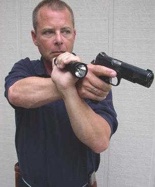 Hand-held flashlight and pistol.