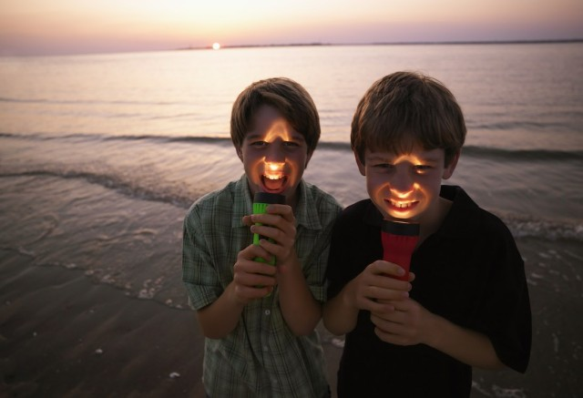 Two boys play with a travel flashlight